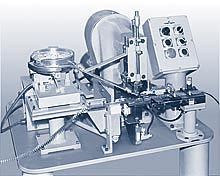 A Model B is complimented with a vibratory bowl for feeding electrical contacts, and an automatic strip feeder for part placement